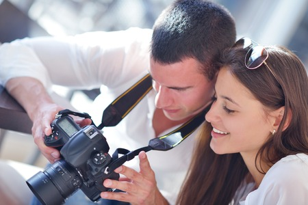 happy young romantic couple looking photos on camera photo