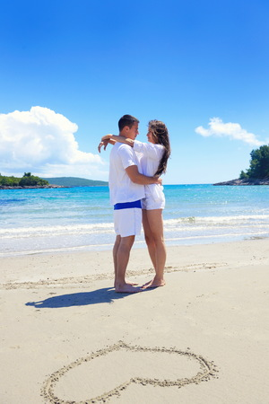 happy young couple have fun and relax  on the summer with heart drawing on beach sand photo