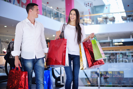 shopping trip: happy young couple with bags in shopping centre mall