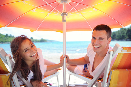 happy young couple have fun and relax  on the beach photo