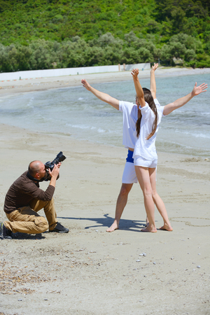 photographer taking photo of models couple on beautiful tropical beach at summer photo