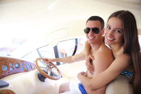 Romantic young couple spending time together and relaxing on yacht photo