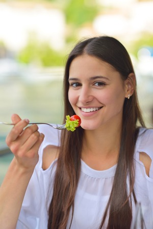 young woman have fresh healthy salad meal lunch at restaurant photo