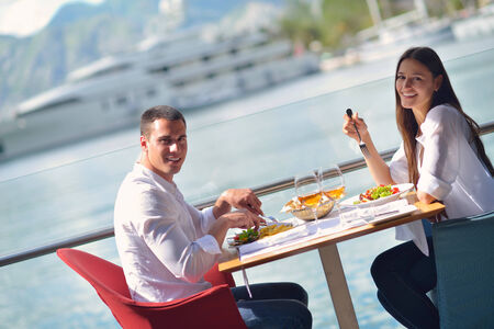 happy young couple having lanch at beautiful restaurant on by the sea on  beach photo