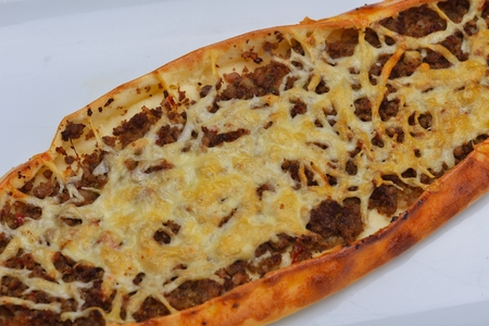 Homemade traditional Turkish meal pide stuffed with meat cheese,  and sauce isolated  photo