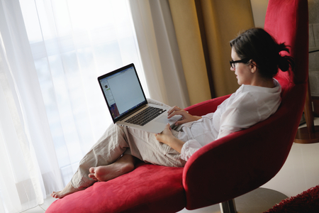 adult, beautiful, beauty, brunette, casual, caucasian, computer, couch, face, female, fun, girl, happy, home, house, indoor, indoors, interior, internet, keyboard, laptop, leisure, life, lifestyle, living, living room, modern, notebook, one, online, peopl Stock Photo