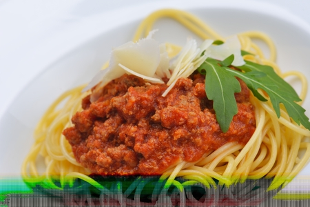 bolognaise: Italian spaghetti topped with bolognaise, or bolognese, sauce with tomatoes, meat and cheese on a plain white plate