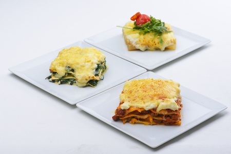 lasagna: Close-up of a traditional lasagna made with minced beef bolognese sauce topped with basil leafs served on a white plate
