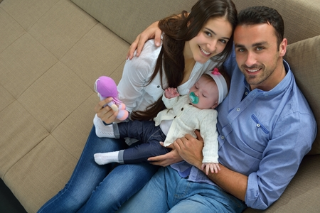 happy young family couple with beautiful new born baby have fun at home photo