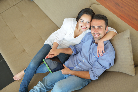 happy young couple at modern home using tablet computer photo