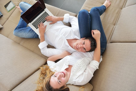 happy young relaxed couple working and playing on laptop computer at home photo