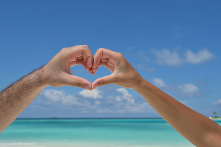 romantic couple make heart shape symbol of love with arms on sunny tropical beach and sea in background photo