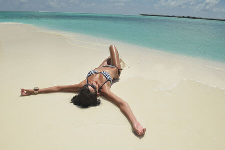 beautiful and happy young woman on beach have fun and relax on summer vacation  over the crystal clear sea photo
