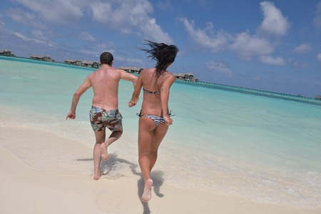 happy young romantic couple in love have fun and relaxing on beautiful beach photo