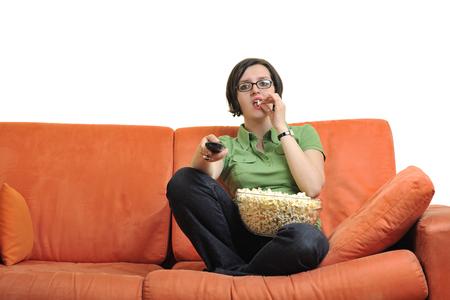 young woman eat popcorn, watching movies and eat popcorn at modern home living room  isolated on white background Stock Photo - 29807207