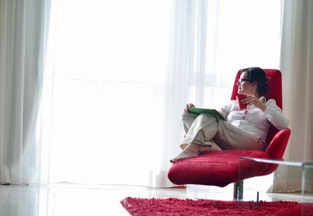A mulher nova em casa relaxando em seu quarto lliving lendo um tablet PC digital de surf internet e trabalho