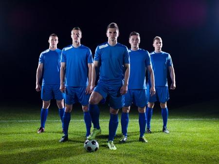 voetballers team groep geïsoleerd op zwarte achtergrond Stockfoto