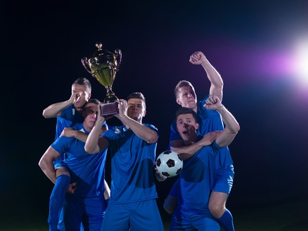 soccer players team group celebrating the victory and become champion of game while holding win coup photo