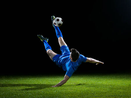 soccer player doing kick with ball on football stadium field\ isolated on black background