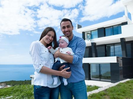 美しい新しい生まれた赤ちゃんの幸せな若い家族カップルは現代家で楽しい時を過す 写真素材