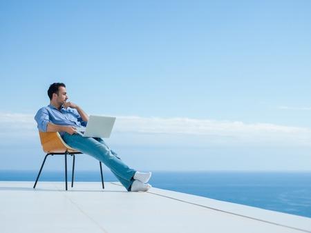 relajado: hombre joven y guapo relajarse y trabajar en el ordenador port�til en el balc�n de casa mientras mira la puesta del sol