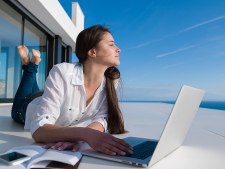modern office space: beautiful young woman relax and work on laptop computer  and read book at modern  home Stock Photo