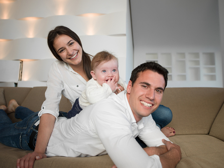 happy young family couple with beautiful new born baby have fun at modern  home photo