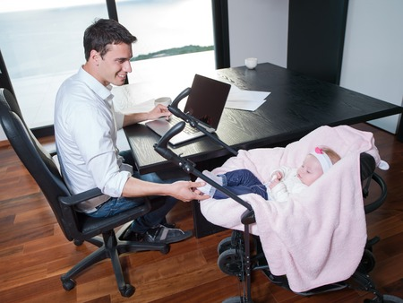 young man parent working on laptop computer at home office and take care of baby photo