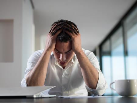 persona confundida: frustrado con problemas joven hombre de negocios que trabajan en la computadora portátil en casa