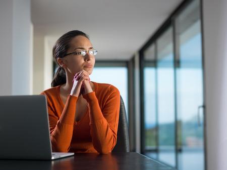 mujeres pensando: Mujer de negocios joven que trabaja en la computadora port�til en la oficina moderna casa