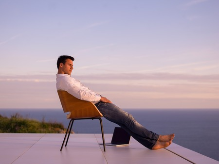 handsome young man relaxing and working on laptop computer at home balcony while looking sunset photo
