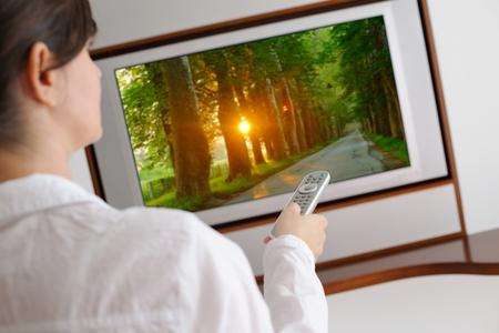 ver tv: mujer joven feliz viendo la televisión en salón moderno hogar