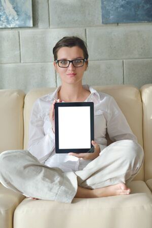 Young woman at home relaxing in her lliving room reading a digital tablet PC surf internet and work photo