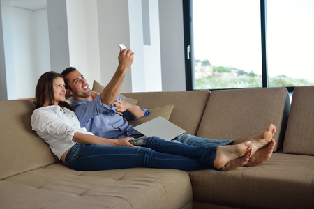 couple couch: Couple on sofa with TV remote