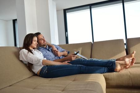 gente sentada: Pareja en el sofá con el control remoto del televisor Foto de archivo