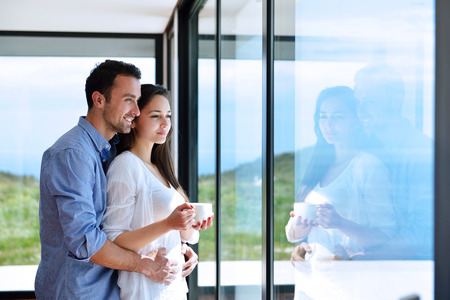 the window: romantic happy young couple relax at modern home indoors Stock Photo