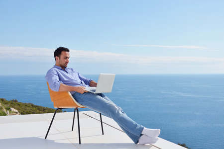 hotel balcony: handsome young man relaxing and working on laptop computer at home balcony while looking sunset