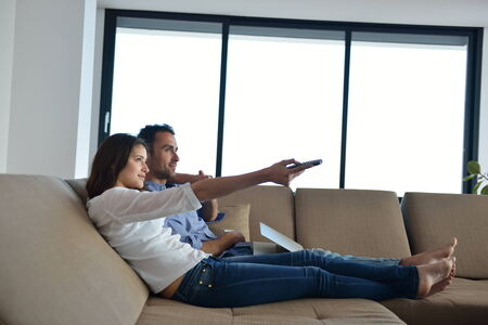 Couple on sofa with TV remote photo