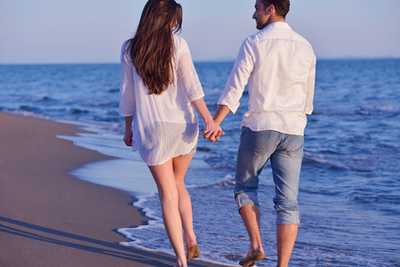 happy young romantic couple in love have fun on beautiful beach at beautiful summer day photo