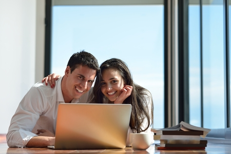 happy young relaxed  couple working on laptop computer at modern home indoor photo