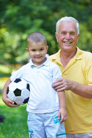 child ball: happy grandfather and child have fun and play in park Stock Photo
