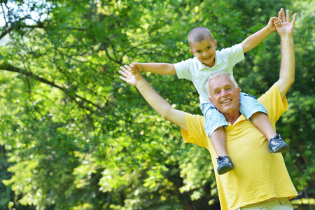 sons and grandsons: happy grandfather and child have fun and play in park Stock Photo