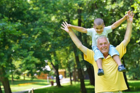 happy old people: happy grandfather and child have fun and play in park Stock Photo