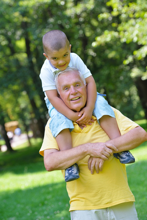 green life: happy grandfather and child have fun and play in park Stock Photo
