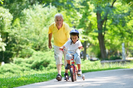 vejez feliz: feliz abuelo y el ni�o se divierten y juegan en el parque Foto de archivo