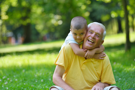 grandfather and grandson: happy grandfather and child have fun and play in park Stock Photo