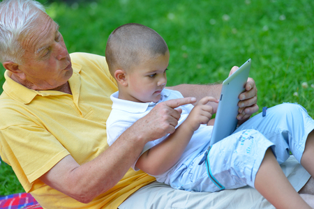 grandsons: grandfather and child in park using tablet computer