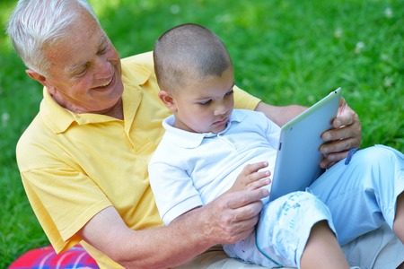 grandfather and child in park using tablet computer photo