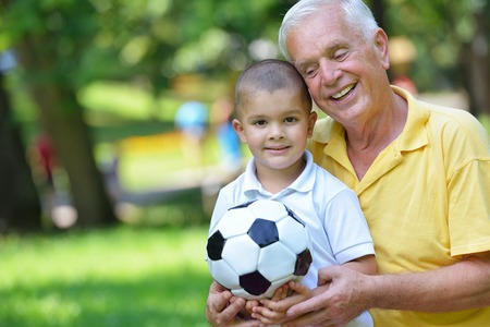 happy grandfather and child have fun and play in park photo