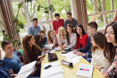 happy young teens group in school on chemisty lessons and library education photo